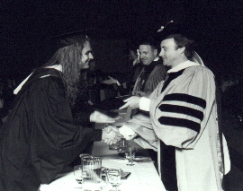 John Ostrosky receiving his degree from Lee Berk, Ahmet Ertegun (not pictured), Al Jareau (not pictured), and Phil Collins at the 1991 Berklee C